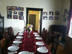 The dining table at the Dorothy Day House is often set for many people, as members of the community often visit for dinner. The walls are lined with pictures of the families that have stayed there.