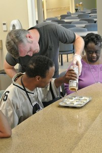 Michael helps Patrick pour the muffin mix in the SRVS Learning Center kitchen.