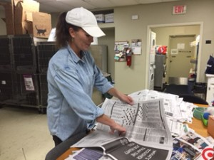 Sorting donated newspapers so dog and cat kennels can be quickly lined by staff and volunteers.